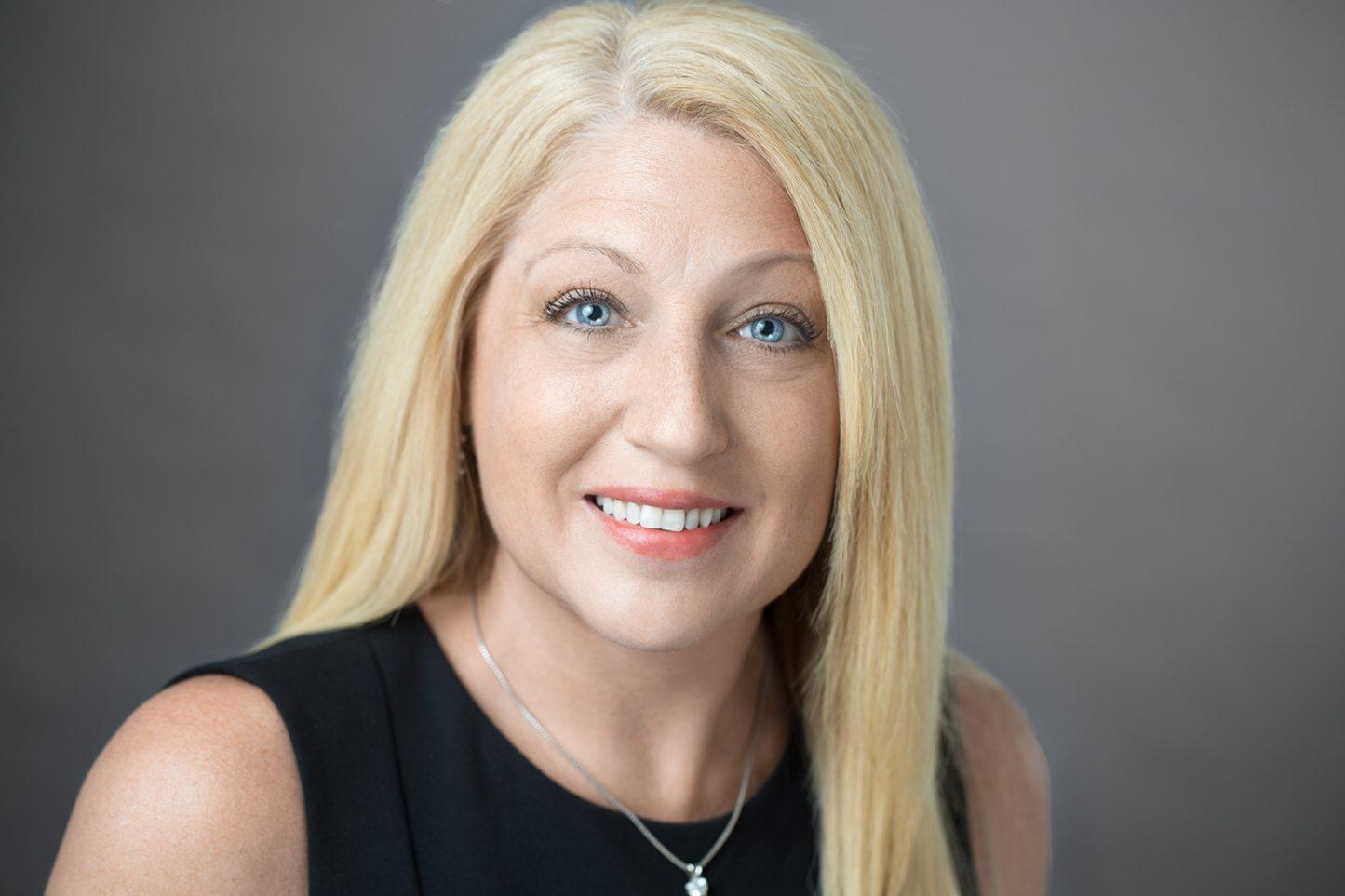Female Headshot Gray Background Blue Eyes