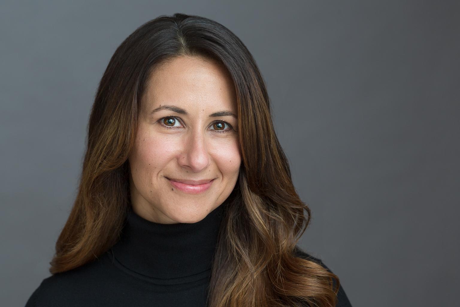 Female Headshot Gray Background Black Turtleneck